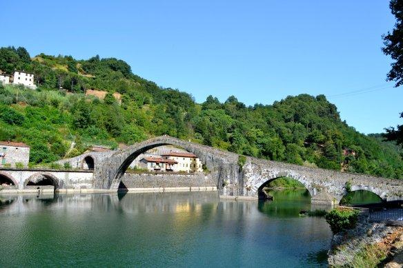"""This medieval, high-arch bridge, the Ponte della Maddellena, is in Borgo a Mozzano and spans the River Serchio. the bridge is known as """"the Devil's Bridge""""."""